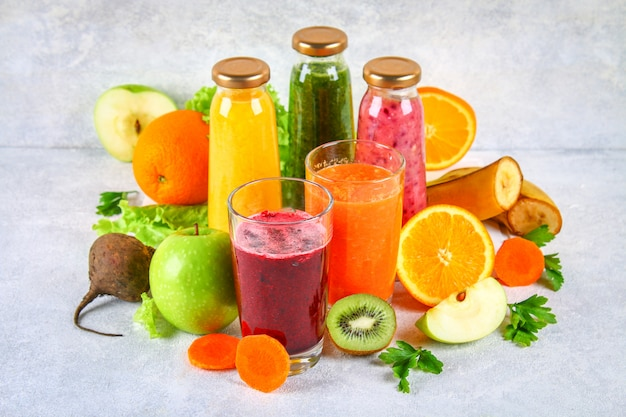 Green, yellow, purple smoothies in currant bottles, parsley, apple, kiwi, orange on a gray table.