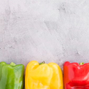 Green; yellow and red bell pepper on grey concrete backdrop