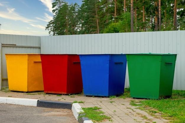 Зеленые, желтые, красные, синие цвета уличные мусорные баки на улице. контейнеры выборочный сбор мусора. концепция раздельного сбора мусора