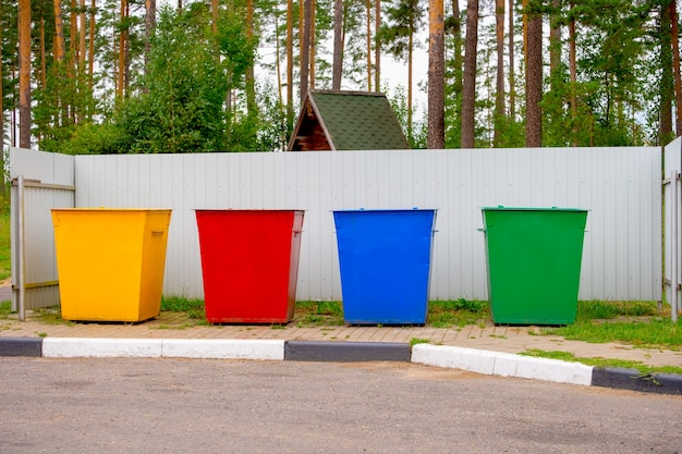 Green, yellow, red, blue color street trash cans on the street. containers selective collection of waste. environmental pollution concept.