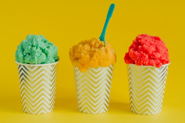 Green, yellow and red fruit ice cream or frozen yogurt in stripped cups