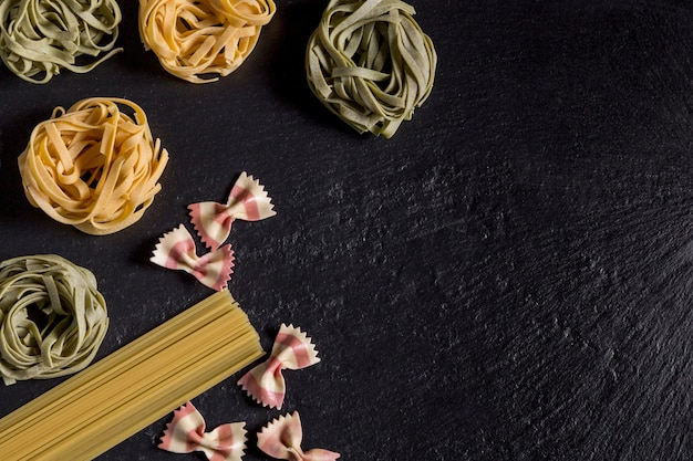 Green and yellow tagliatelle, spaghetti and pasta butterflies on black slate