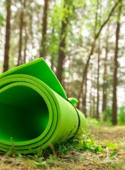 緑のヨガマットが地面に横たわってクローズアップ公園の屋外トレーニング機器