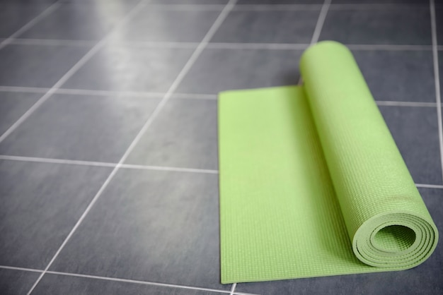 Green yoga mat on gray tile floor