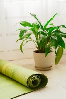 自宅の部屋のヨガクラスの緑のヨガマット