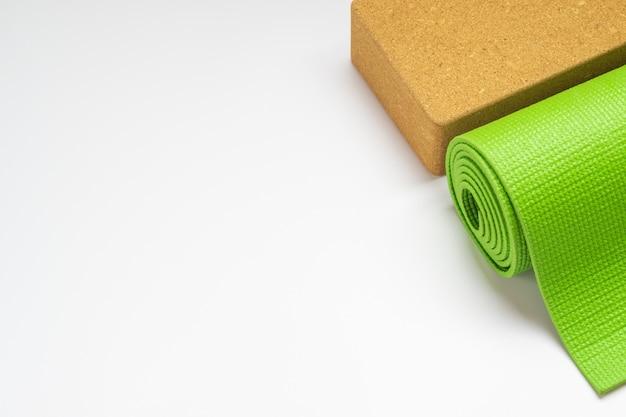 Green yoga mat and yoga blocks on white