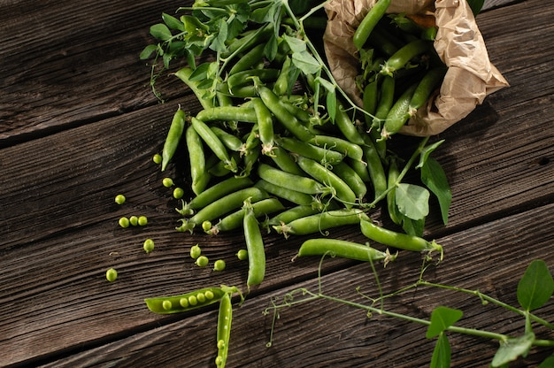 Green young peas in pods, freshly picked on old brown boards, top view, empty space for text