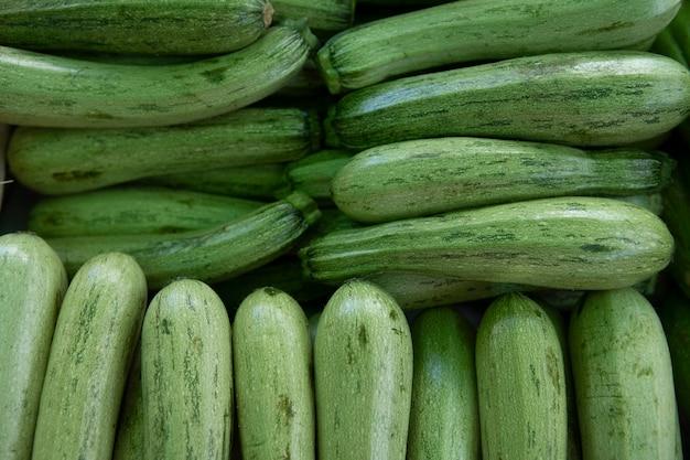 緑のズッキーニ。細長い緑の野菜。野外市場で提供される新鮮な摘みたてのグリーンズッキーニ。夏のスカッシュ