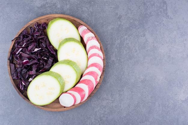 木製の大皿に刻んだ紫キャベツと緑のズッキーニスライス