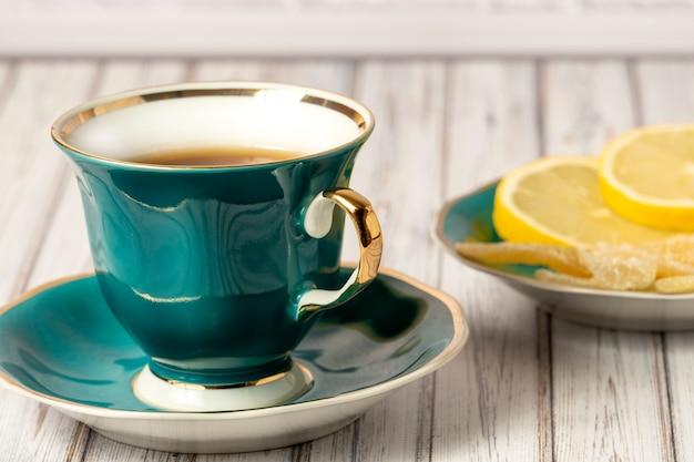 木製のテーブルにレモンと生greenの砂糖漬けの熱いお茶とソーサーのグリーンカップ。閉じる