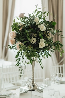 Greenery bouquet with roses stand on the feast table