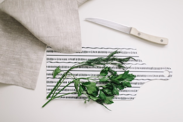 Зелень свежей петрушки на разделочной доске на белом