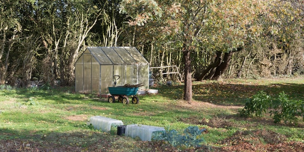 Greenhouse made of polycarbonate with a triangular roof in a corner of the garden