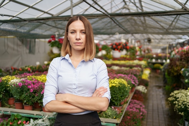 Greenhouse owner posing with folded arms having many flowers and a colleague holding a pot with pink chrysanthemums under glass roof