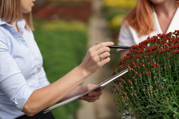 Greenhouse owner presenting flowers options to a potential customer retailer.