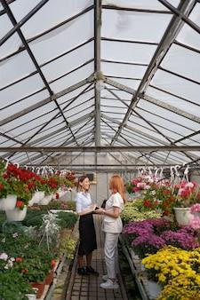 Владелец теплицы представляет варианты цветов потенциальному продавцу.