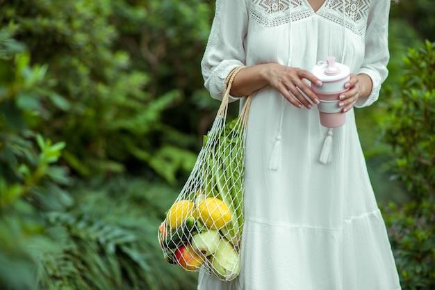 温室。野菜の袋と手のこぼれ防止カップの白いドレスを着た女性
