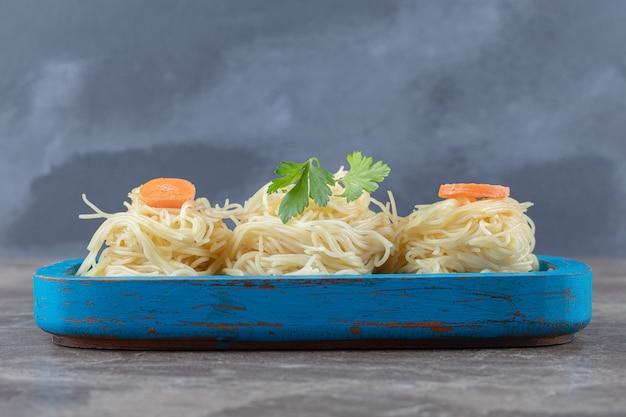 스파게티, 나무 보드, 대리석에 채소와 강판 당근.