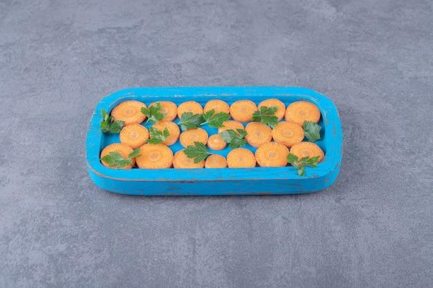 Зелень и нарезанная морковь на деревянном подносе, на мраморной поверхности.