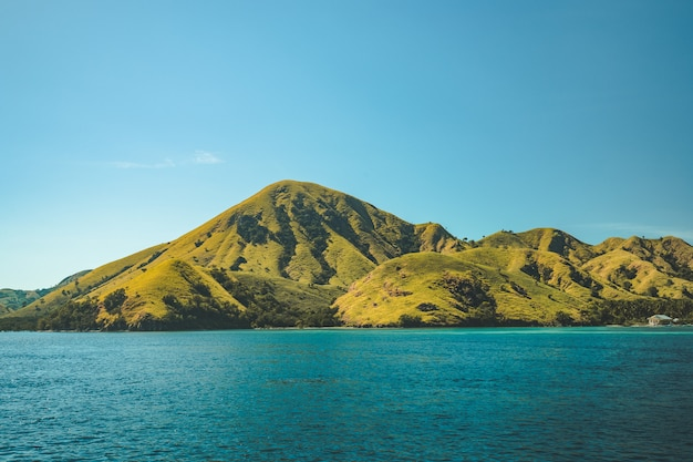 Greens covered hills washed by calm ocean. komodo.