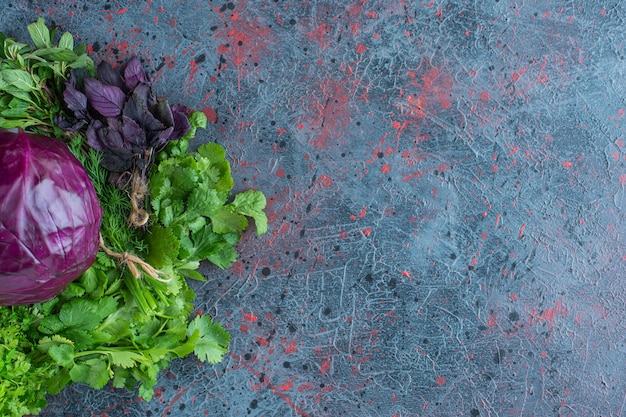 Greens and purple cabbage, on the marble background.