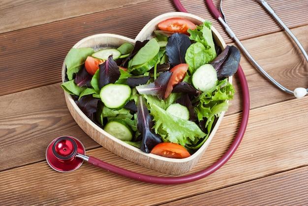 Салат из зелени в форме сердца деревянные пластины и стетоскоп.