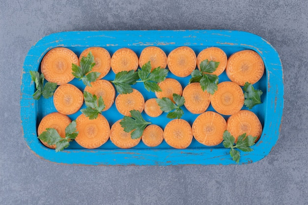 Greens and sliced carrot on the wooden tray , on the marble surface.
