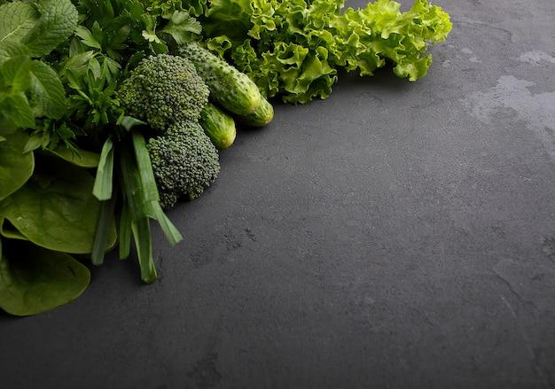 Greens: spinach, cucumber, broccoli, garlic, mint, parsley, lettuce, onion on a black background