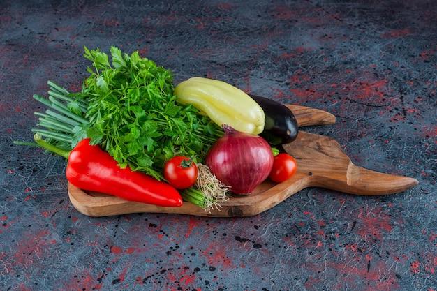 Verdi e verdure su un tagliere, sullo sfondo di marmo.