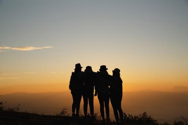 Группа друзей, стоя вместе на greensward и наслаждаясь собой.