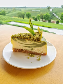 Greentea cheesecake on a white plate on a wooden table