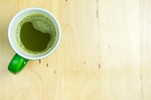 Greentea cup on wooden background. top view, flat lay concept.