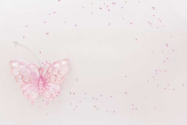 Greeting birthday card with copy space. girly composition of glitter and pink butterfly toy. flat lay
