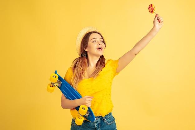 인사, 전화. 노란색 스튜디오 배경에 백인 여자의 초상화입니다. 모자에 아름 다운 여성 모델입니다. 인간의 감정, 표정, 판매, 광고의 개념. 여름철, 여행, 리조트.