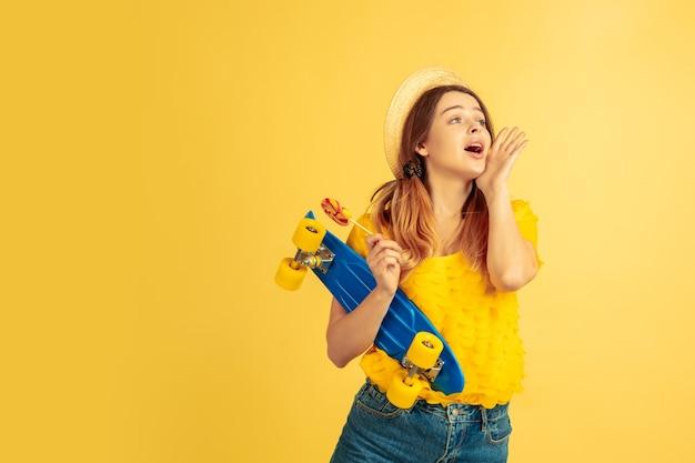 인사, 전화. 노란색 스튜디오 배경에 백인 여자의 초상화입니다.