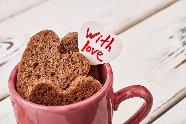 Открытка и хлеб сердца. розовая чашка на деревянной поверхности. радость ощущать любовь.