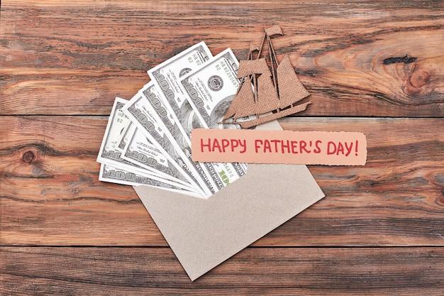 グリーティングカード、合板船、お金。父の日カードとドル。贈り物としての航海。