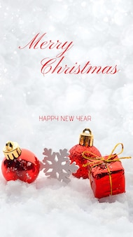Greeting card for christmas and new year decorations red toys balls on the snow sparkling silver background banner with copy space. white snowflakes bokeh. text.