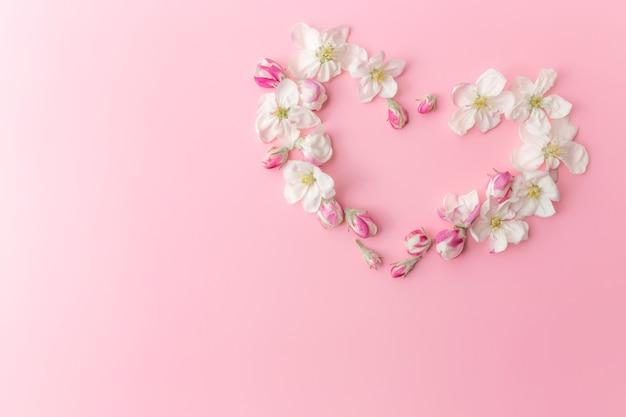グリーティングカードのコンセプトフラットは、リンゴの花のハート型の飾りの境界線とピンクの背景に横たわっていた。高品質の写真