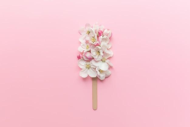グリーティングカードのコンセプトフラットは、スティックにリンゴの花のアイスクリームキャンディーとピンクの背景に横たわっていた。高品質の写真