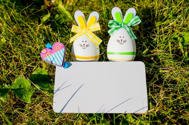 Greeting card and easter eggs on green grass