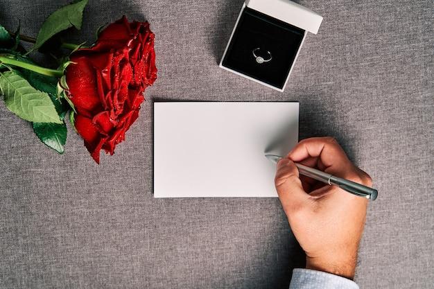 グリーティングカード、婚約指輪、赤いバラをプレゼント。バレンタインデーと結婚の概念。