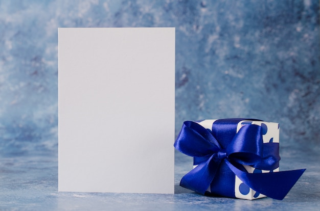 Greeting card for father's day or birthday. gift box with blank white paper on blue background.