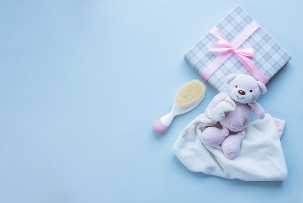 Поздравительная открытка на рождение девочки с подарком плюшевого мишки и детской щеткой для волос на светло-серой поверхности изображение с копией пространства