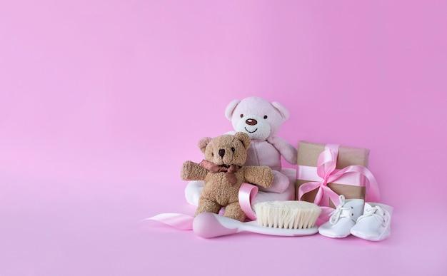 핑크색 표면 이미지 복사 공간에 테디 베어와 아기 헤어 브러시와 아기 소녀 탄생을위한 인사말 카드