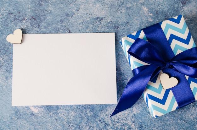 父の日や誕生日のグリーティングカード。青の背景に空白のホワイトペーパーとギフトボックス。
