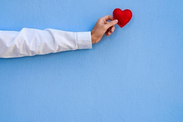Открытка на день святого валентина с копией пространства для текста. красное сердце в мужской руке на синем фоне