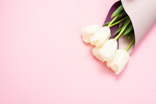 母の日または3月8日のグリーティングカード。ピンクのパステル調の背景に白いチューリップの春の新鮮な花束。あなたのテキストや広告のための場所