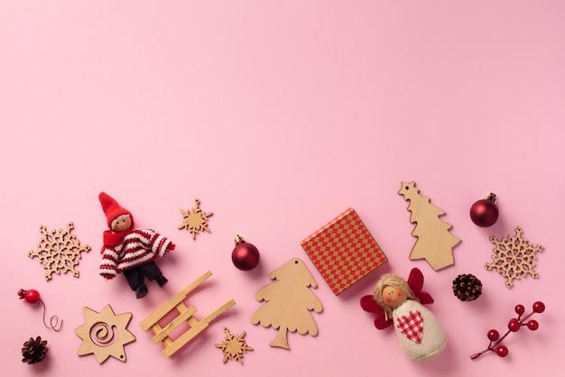 Открытка на новый год. рождественские подарки, декоративные элементы и украшения на розовом фоне.