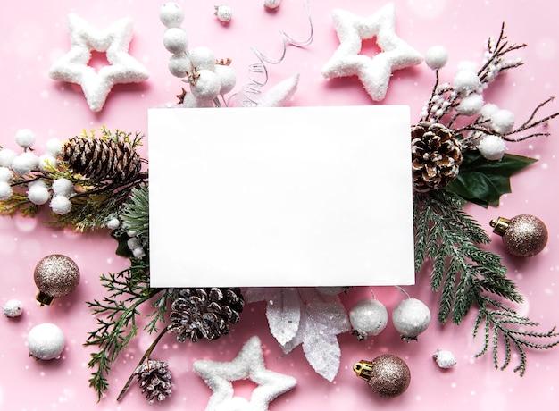 クリスマス休暇のグリーティングカード。ピンクの背景にトウヒの枝、コーン、装飾。上面図